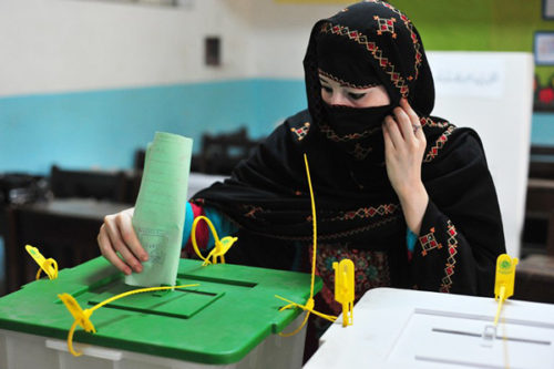 A Pakistani resident casts her ballot at a polling station during general elections in Rawalpindi on May 11, 2013. A bomb attack targeting an election candidate has killed 11 people in Pakistan's financial hub of Karachi as historic polls got under way, a hospital doctor said.   AFP PHOTO/Farooq NAEEM